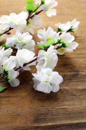 flowering sakura tree branches (artificial) on a wooden background photo