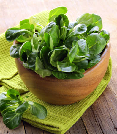 Fresh green salad valerian in a wooden bowl  Stock Photo