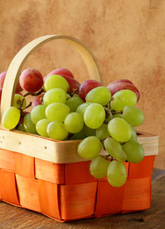 Red and green grapes in a wicker basket Stock Photo - 18563206