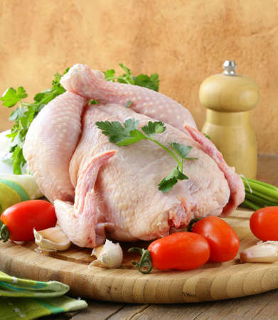 fresh raw chicken on a cutting board with vegetables and herbs photo