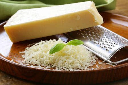 queso rayado: de queso parmesano rallado y rallador de metal en la placa de madera