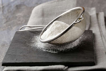 icing sugar: powdered sugar in a metal strainer on a gray background Stock Photo