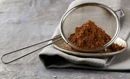 cocoa powder in a metal sieve with a gray background photo