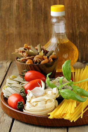 Various types of pasta (spaghetti, fettuccini, penne) and tomato photo