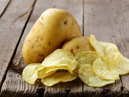 natural potato chips and fresh potato on a wooden background Stock Photo - 18931321