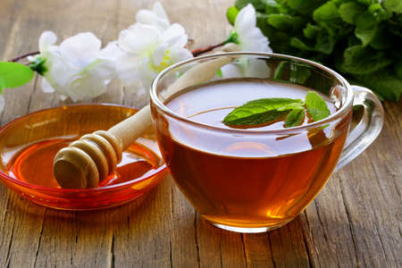 cup of tea with mint and honey on a wooden table photo
