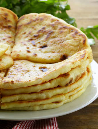 indian cooking: pile of fried bread with butter and parsley