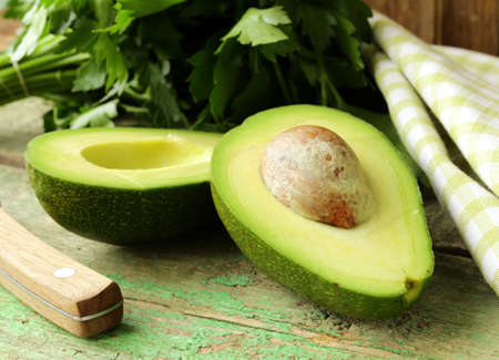 ripe avocado cut in half on a wooden table Stock Photo