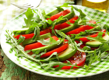 avocado salad with arugula, tomato and olive oil photo