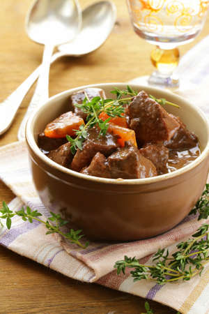 beef goulash  stew   with vegetables and herbs on a wooden table