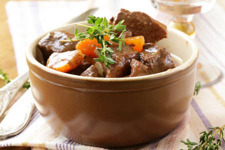 goulash: beef goulash  stew   with vegetables and herbs on a wooden table
