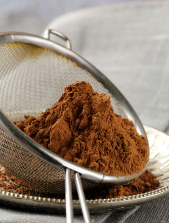 cocoa powder in a metal sieve on gray background photo