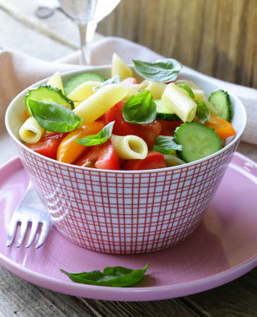 pasta salad with cucumbers, tomatoes and basil photo