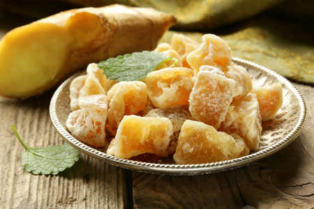 candied: sugared ginger  candied  and fresh root on a wooden table