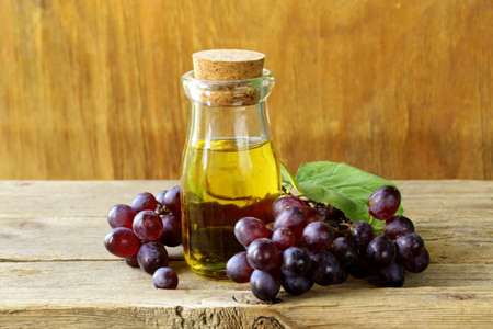 grape seed: bottle with grape seed oil on a wooden table Stock Photo