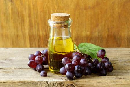 bouteille avec de l'huile de pépins de raisin sur une table en bois