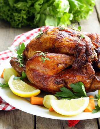 roasted chicken with herbs served on a plate with vegetables and grapes photo