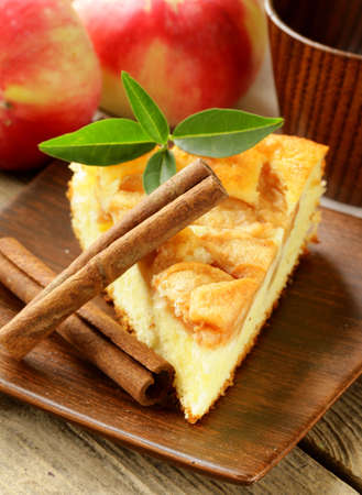 piece of homemade apple pie with cinnamon on a wooden table photo