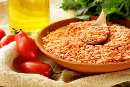 red lentils in a clay bowl on a wooden table