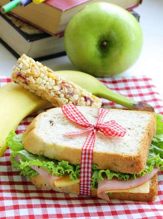 Sandwich mit Schinken, Apfel, Banane und Müsliriegel - gesunde Ernährung, Mittagessen in der Schule