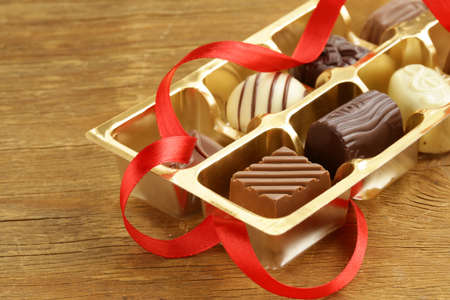 gift box of chocolate candies on a wooden background photo