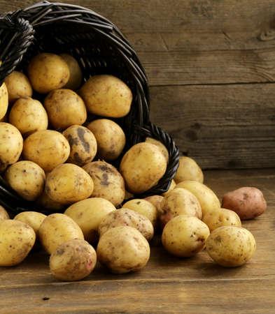 potato basket: fresh organic potatoes on a wooden background, rustic style