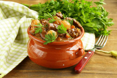 Beef stew with vegetables and herbs in a clay pot - comfort food Stock Photo