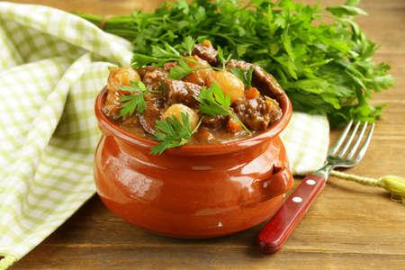 Ragoût de boeuf avec des légumes et des herbes dans un pot en argile - la nourriture de confort