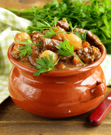 goulash: Beef stew with vegetables and herbs in a clay pot - comfort food Stock Photo