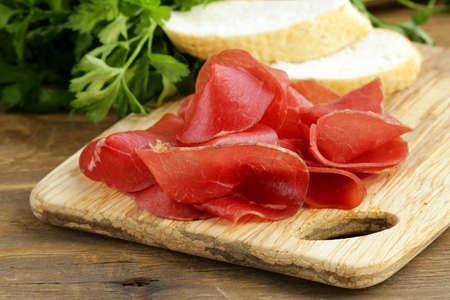 Smoked meat bresaola on a cutting board  Stock Photo
