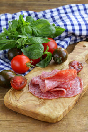 smoked sausage, tomatoes and basil on a wooden cutting board photo