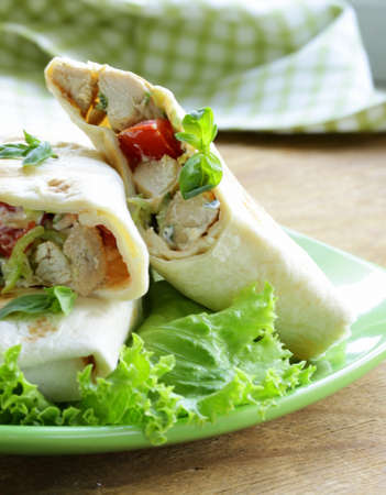 burrito  doner  with chicken and vegetables wrapped in pita bread photo