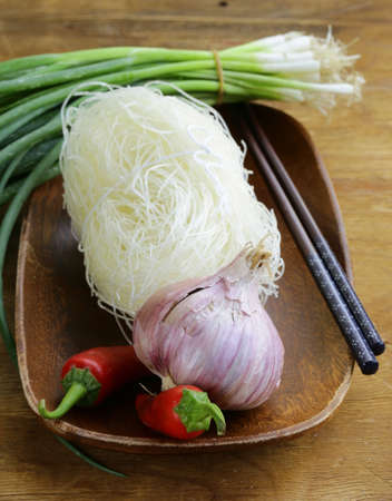 Asian food ingredients - rice noodles, ginger, chili pepper, garlic photo
