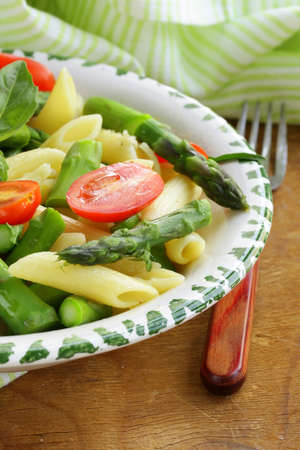penne pasta with tomatoes and asparagus, fresh spring food photo