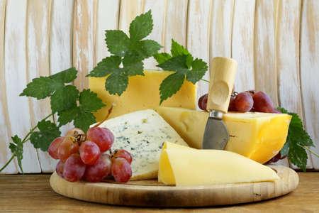 tabla de quesos: tabla de quesos Maasdam, Roquefort, Camembert y uvas de postre