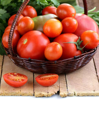 basket with different types of tomatoes on wooden table photo
