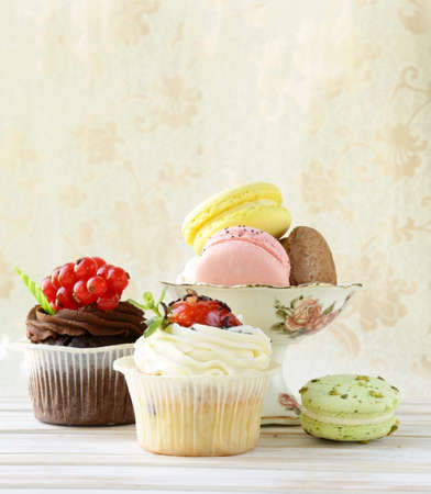 dessert stand: holiday desserts, cupcakes and macaroons on a vintage background