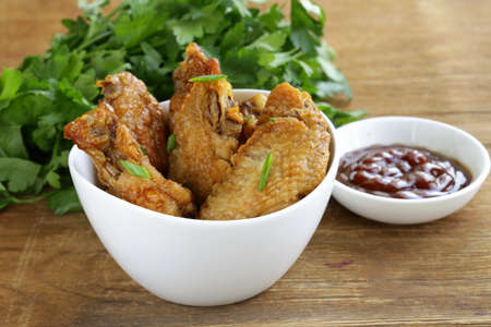Fried chicken wings with hot  sauce in a white bowl photo