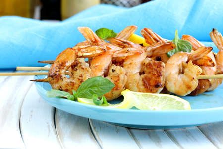shrimp grilled on wooden skewers with lemon and basil photo