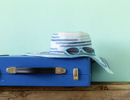old fashioned: old fashioned blue suitcase for travel and beach hat on a turquoise background Stock Photo