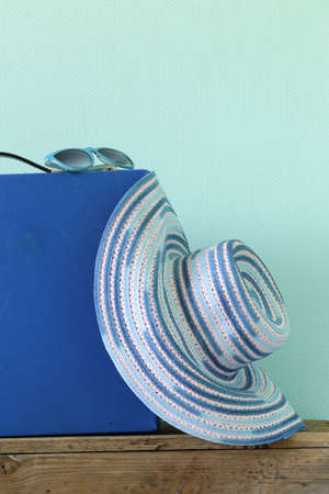 old fashioned blue suitcase for travel and beach hat on a turquoise background photo