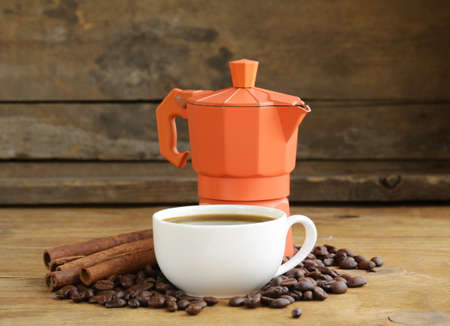 Still life of coffee beans, coffee pot and cup of espresso on vintage wooden background  photo
