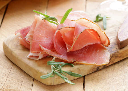 parma ham  jamon  sliced on a wooden board photo