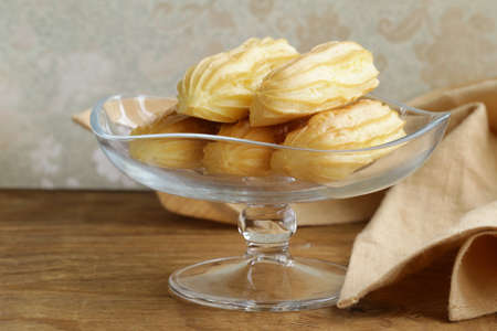 choux pastry eclairs on glass stand base, festive dessert photo