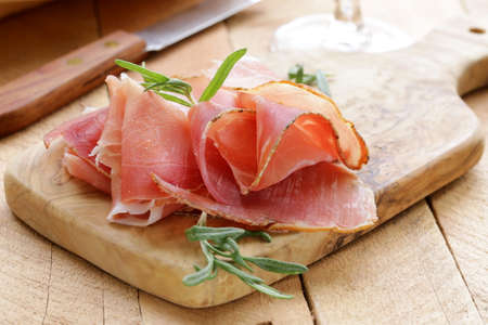 parma ham  jamon  sliced on a wooden board