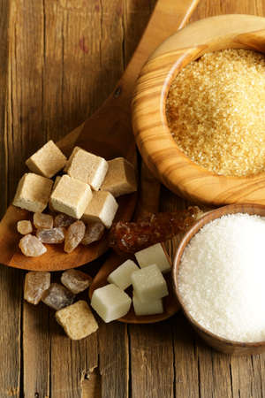 different kinds of sugar - brown, white, refined sugar on a wooden background photo
