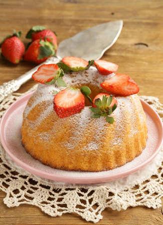 round sponge cake with strawberries and powdered sugar Stock Photo