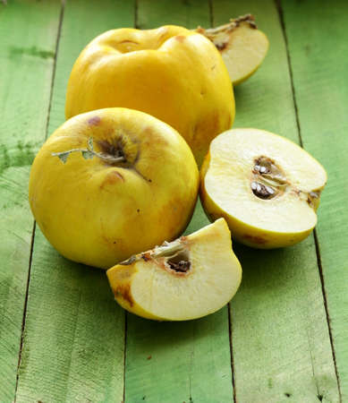 quince: ripe yellow quince on a wooden table