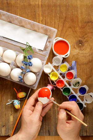 Coloring Easter eggs  hand in the shot   paint and brushes photo