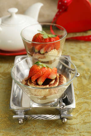 Italian dessert tiramisu decorated with strawberries in a glass beaker photo
